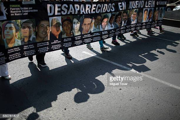 People hold a long banner with photographs of their disappeared relatives during a march on Mother's Day on May 08 2016 in Mexico City Mexico Mothers...