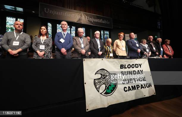 People hold a minute silent during the press conference at the Guildhall in Londonderry Northern Ireland after the announcement from the Public...