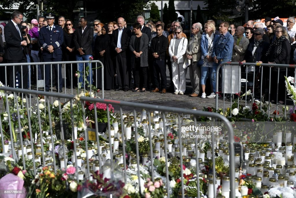 People hold a minute's silence in front of flowers and candles laid at a makeshift memorial at the Turku Market Square in Turku, Finland, on August 20, 2017. Ten people were stabbed in Central Turku on August 18, 2017 and two persons have been confirmed dead. / AFP PHOTO / Lehtikuva / Vesa Moilanen / Finland OUT