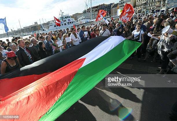 People hold a Palestinian flag during a demonstration on June 1 2010 in Marseille southern France to protest against Israel's deadly raid on an aid...