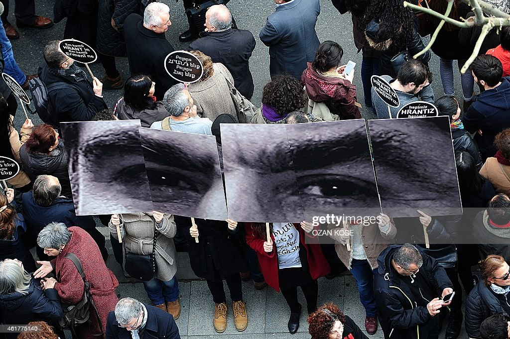 People hold a picture showing slain journalist Hrant Dink's eyes in front of Armenian newspaper 'Agos' during a commemoration ceremony for Dink, in Istanbul, on January 19, 2015. Turkish riot police were out in force as large crowds massed in Istanbul to demand justice for a prominent Turkish Armenian journalist murdered eight years ago. Hrant Dink, one of the most prominent voices of Turkey's shrinking Armenian community, was killed by a gunman on January 19, 2007. The 52-year-old Dink, a prominent member of Turkey's tiny Armenian community, campaigned for reconciliation but was hated by Turkish nationalists for calling the World War I massacres of Armenians a genocide.