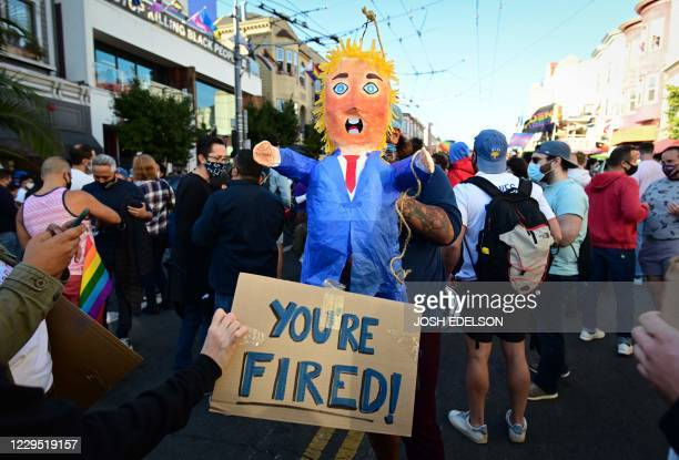 TOPSHOT People hold a pinata of US President Donald Trump as people celebrate Joe Biden being elected President of the United States in the Castro...