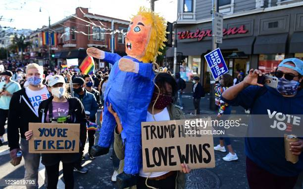 People hold a pinata of US President Donald Trump as people celebrate Joe Biden being elected President of the United States in the Castro district...