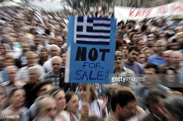 People hold a placard depicting the Greek flag and 'not for sale' during a massive protest rally against austerity measures organized by Universities...