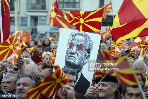 TOPSHOT People hold a placard dipicting billionaire George Soros during a demonstration against a deal between Social Democrats and the Albanian...