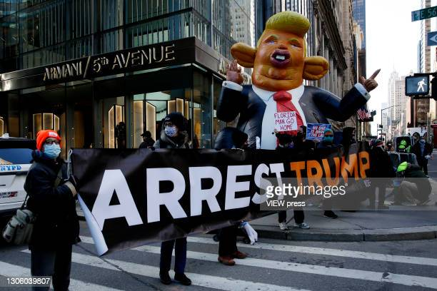 People hold a placard during a protest against the former U.S. President Donald Trump at Trump Tower on March 08, 2021 in New York. Trump is...
