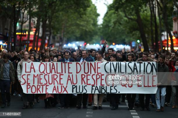 """People hold a placard reading """"the quality of a civilization is measured by the respect it gives to the weakest"""" as they take part in a white march,..."""