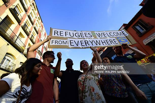 People hold a placard welcoming refugees during a rally in support of migrants and refugees as part of the European Day of Action in Madrid on...