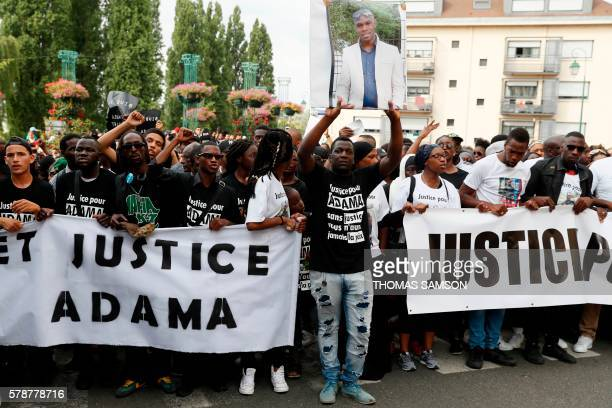 People hold a portrait picture of Adama Traore and a banner reading 'Truth and justice for Adama' as they attend a white march organised in tribute...