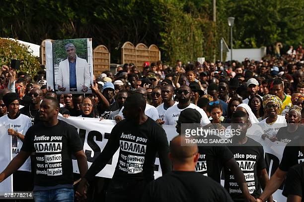 People hold a portrait picture of Adama Traore and wear Tshirts reading 'Justice for Adama' as they attend a white march organised in tribute to the...