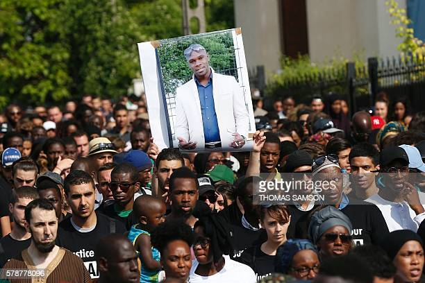 People hold a portrait picture of Adama Traore as they attend a white march organised in tribute to the 24year old man in BeaumontsurOise on July 22...