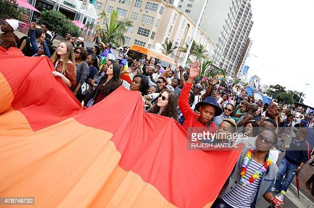 People hold a rainbow flag as they take part in the annual Gay Pride Parade at Durban's North Beach as part of the threeday Durban Pride Festival in...