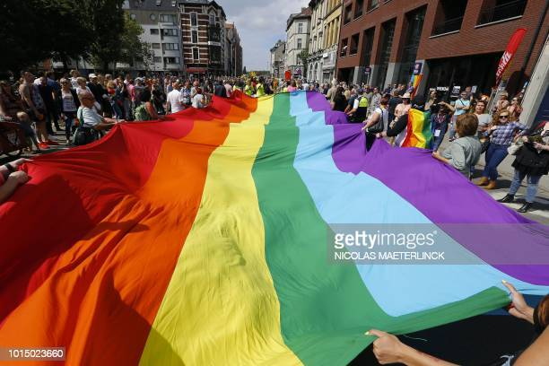 People hold a rainbow giant flag as they take part in the 11th edition of the Antwerp Pride parade a Lesbian Gay Bisexual and Transgender Pride march...