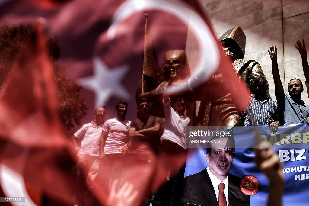 TOPSHOT - People hold a Recep Tayyip Erdogan's picture during a demonstration in support to the Turkish President at the Sarachane park in Istanbul on July 19, 2016. The Turkish army said on July 19 that the vast majority of its members had no links with the July 15 attempted coup and warned that the putschists would face severe punishment. The armed forces blamed the 'Fethullah Terrorist Organisation' (FETO) for the failed putsch, referring to Fethullah Gulen, a one-time ally turned foe of President Recep Tayyip Erdogan. Turkey's prime minister said on July 19 his government had sent four files to the United States, as Ankara seeks the extradition of US-based preacher Fethullah Gulen. / AFP / ARIS
