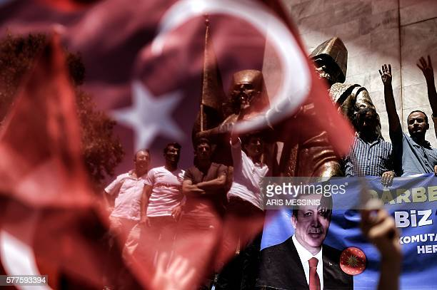 TOPSHOT People hold a Recep Tayyip Erdogan's picture during a demonstration in support to the Turkish President at the Sarachane park in Istanbul on...