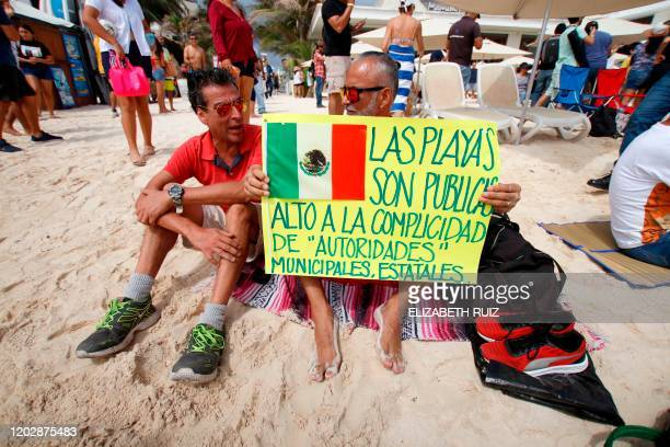 People hold a sign depicting the Mexican flag and reading The beaches are public Stop complicity with state municipal authorities as they take part...