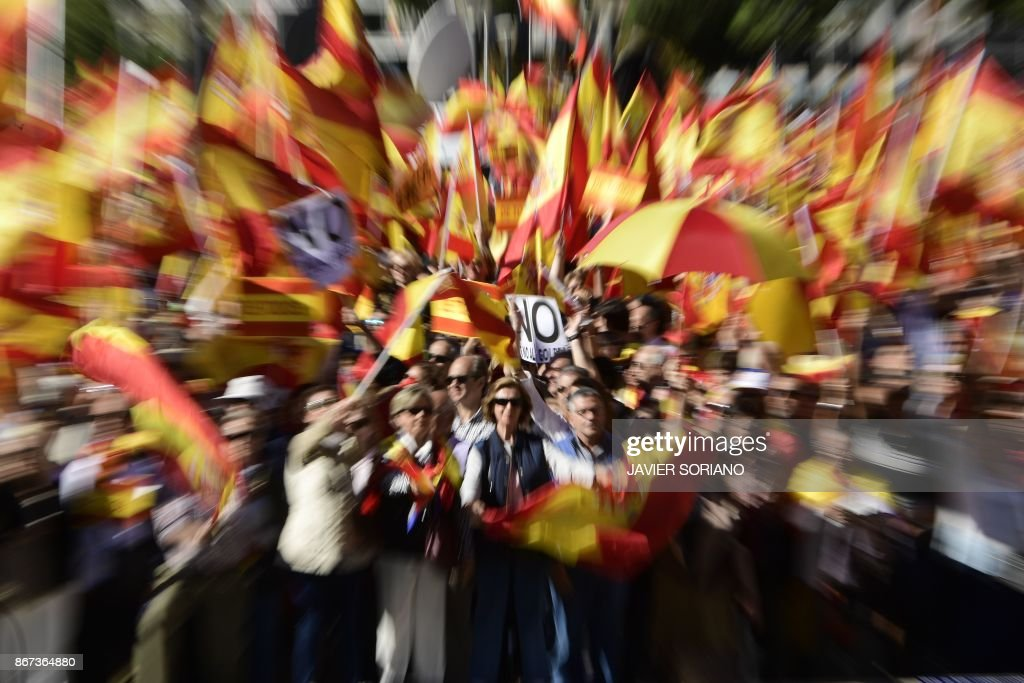 TOPSHOT - People hold a sign reading 'No to the coup' while waving Spanish flags during a demonstration calling for unity at Plaza de Colon in Madrid on October 28, 2017, a day after direct control was imposed on Catalonia over a bid to break away from Spain. Spain moved to assert direct rule over Catalonia, replacing its executive and top functionaries to quash an independence drive that has plunged the country into crisis and unnerved secession-wary Europe. /