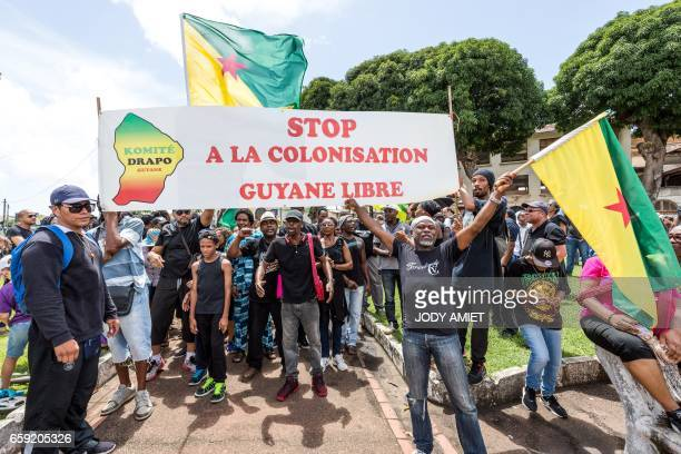 People hold a sign reading 'Stop colonisation Free French Guiana' during a march in support of the general strike in Cayenne on the French overseas...