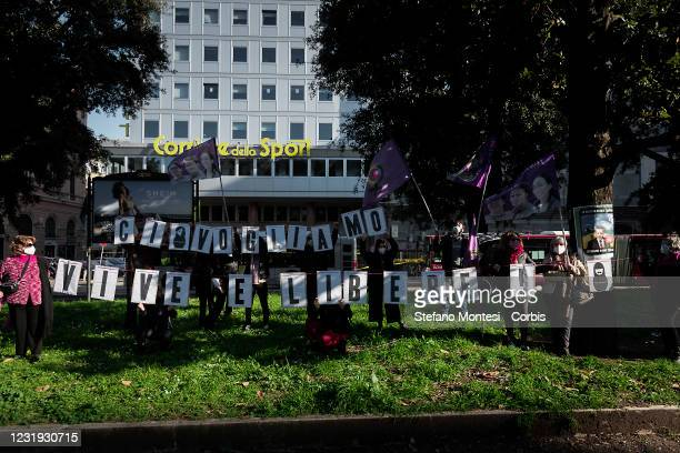 """People hold a sign reading: """"We want us to be alive and free"""" during a protest against Turkey's decision to withdraw from the Istanbul Convention on..."""