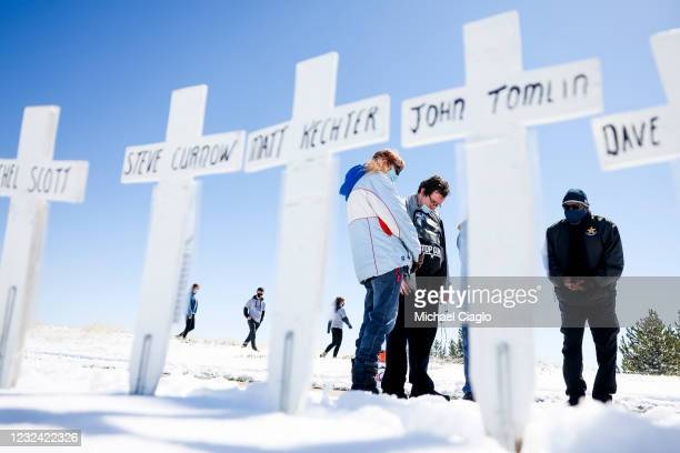 People hold a small prayer service next to crosses with the names of the victims of the Columbine High School shooting near the Columbine Memorial on...