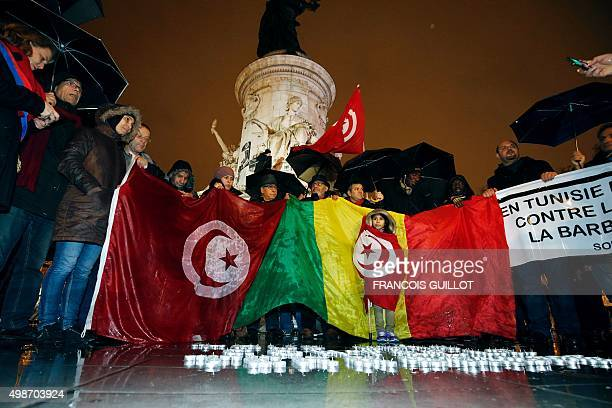 People hold a Tunisian and a Malian flag on the Place de la Republique in Paris on November 25 during a gathering to commemorate the victims of...