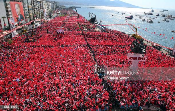 People hold a Turkish flag as Turkish President Recep Tayyip Erdogan addresses the crowd during 'Izmir Gathering' which is also attended by Turkey's...