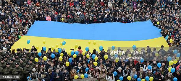 People hold a Ukrainian flag and sing national anthem on March 10 2016 downtown western Ukrainian city of Lviv during a demonstration to mark 151th...