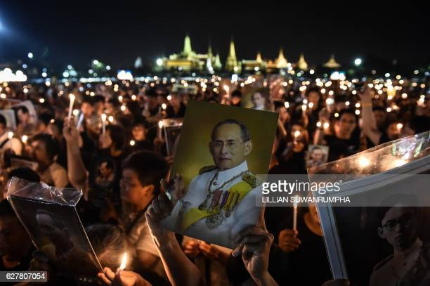 People hold aloft images of the late Thai King Bhumibol Adulyadej to commemorate his birthday in Sanam Luang park in front of the Grand Palace in...