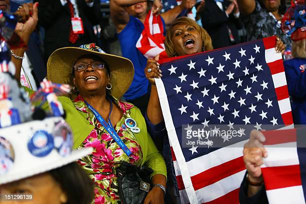 People hold American flags as they cheer during day two of the Democratic National Convention at Time Warner Cable Arena on September 5 2012 in...