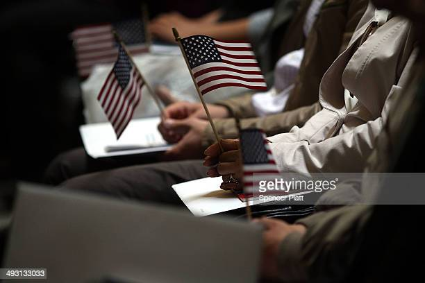 People hold American Flags during a naturalization ceremony at Federal Hall for approximately 75 citizenship candidates from 31 countries on May 22...