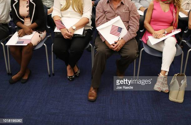 People hold an American flag as they participate in a ceremony to become an American citizen during a US Citizenship Immigration Services...