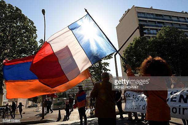 People hold an Armenian and a French flag during a march in commemoration of the 101th anniversary of the mass killings of Armenians by Ottoman...
