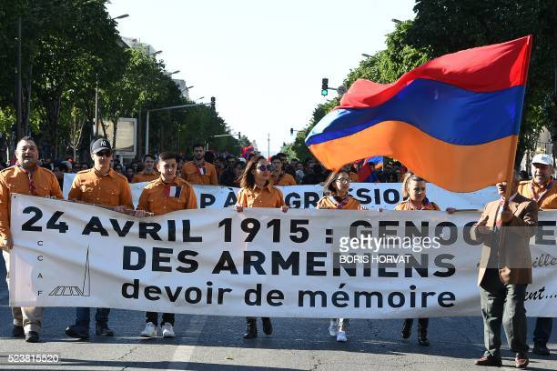 People hold an Armenian flag and a banner which translates as April 24 2015 genocide of the Armenians duty of memory during a march in commemoration...