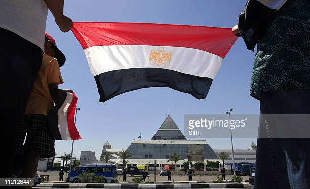 People hold an Egypt's flag as they stand outside Sharm elSheikh hospital where former president Hosni Mubarak was admitted after he reportedly...
