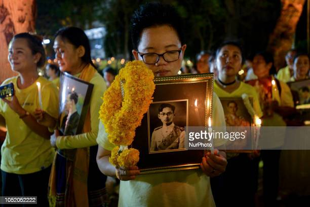People hold an image of late Thai King Bhumibol Adulyadej during a making 2 year anniversary of the Thai King Bhumibol Adulyadej's death at Siriraj...