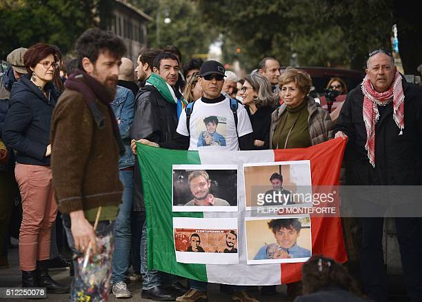 People hold an Italian flag with photos of Giulio Regeni a Cambridge University PhD student who was found dead bearing signs of torture after...