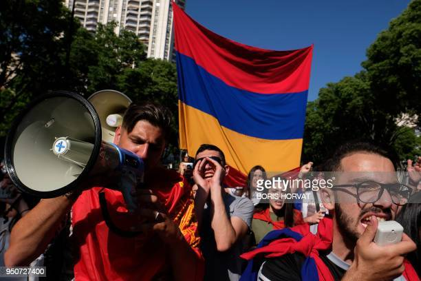 People hold Armenian flags and shout during a march in commemoration of the 103rd anniversary of the mass killings of Armenians by Ottoman forces in...