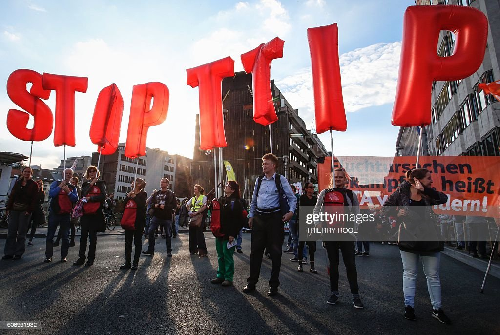 People hold balloons reading 'Stop TTIP' during a demonstration outside the European Union headquarters in Brussels, on September 20, 2016 to protest against huge transatlantic trade deals linking Europe with Canada and the United States. Several thousand The protests came after mass rallies in German cities on September 17, 2016 against the European Union's planned Transatlantic Trade and Investment Partnership (TTIP) with the United States, and the Comprehensive Economic and Trade Agreement (CETA) with Canada. / AFP / BELGA AND Belga / THIERRY