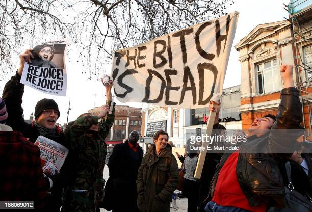 People hold banenrs and signs aloft as they celebrate the death of former British Prime Minister Margaret Thatcher following the announcement of her...
