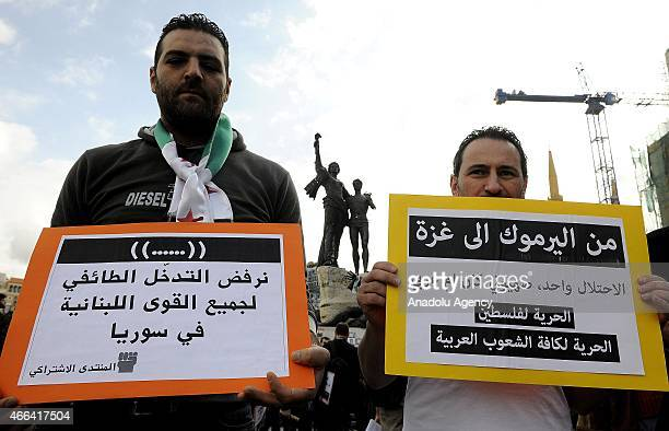 People hold banners and flags as they shout slogans during a protest against Bashar Assad regime on the 4th year of the Syrian civil war in Beirut...