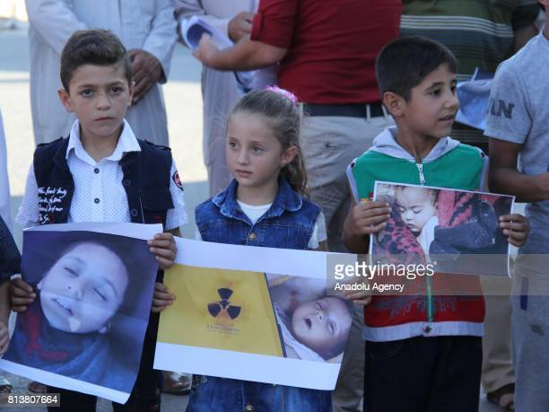 People hold banners and pictures during the commemoration of 100th anniversary day of Assad Regime's chemical attack on Khan Shaykun district of...