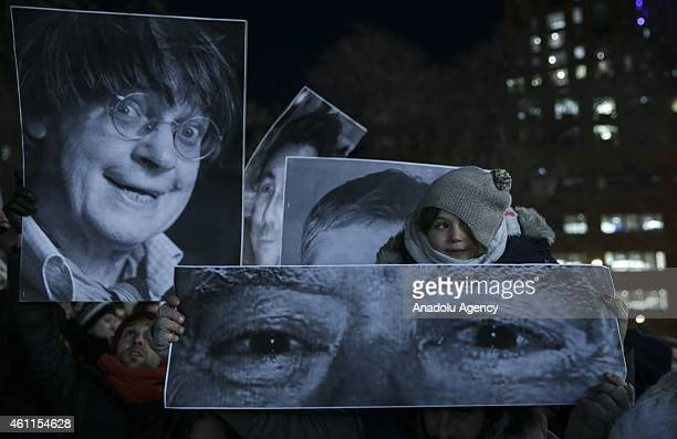 People hold banners and posters to show reactions against gun attack on the building of French magazine 'Charlie Hebdo' in Paris leaving 12 dead...