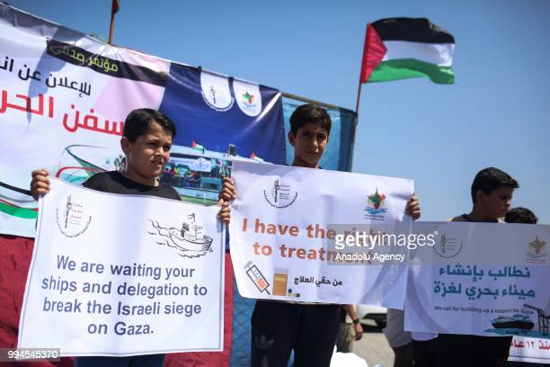 People hold banners as Bassam Manasra a spokesman for Gazas National Committee for Breaking the Siege and speaks at a press conference in Gaza City...