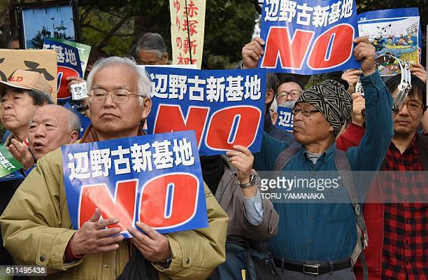 People hold banners as they listen to a speaker during a rally against a new US military base in Okinawa Japan's nouthernmost prefecture in front of...