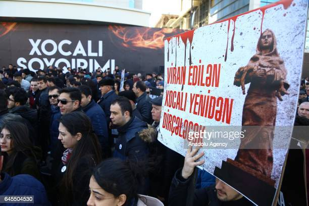 People hold banners at Ana feryadi monument during the 25th anniversary of Khojaly Massacre in Baku Azerbaijan on February 26 2017 The massacre on...