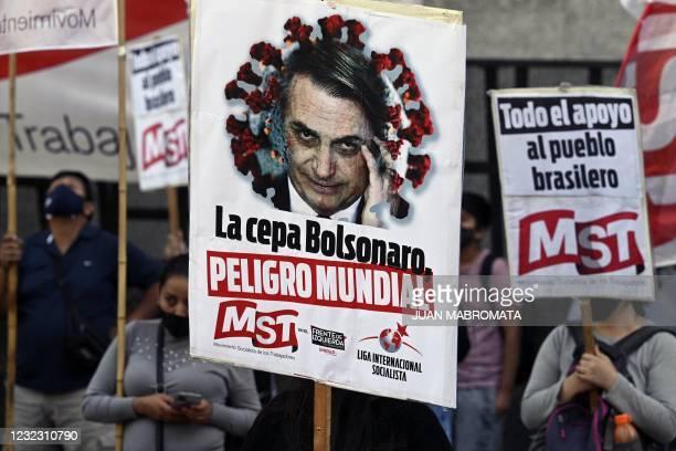 "People hold banners depicting Brazil's President Jair Bolsonado reading ""The Bolsonaro strain, world danger"" during a protest of members of leftist..."