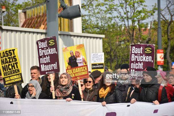People hold banners during a counter protest against an Identitarian protest in front of the Justice Ministry on April 13 2019 in Vienna Austria...