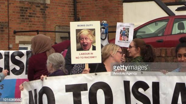 People hold banners during a protest, organized by Stand Up To Racism platform, against former British Foreign Secretary Boris Johnson after his...