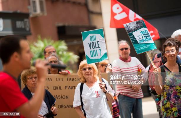 People hold banners during a protest to support Nicole Briend an activist of the Association for the Taxation of Financial Transactions and for...