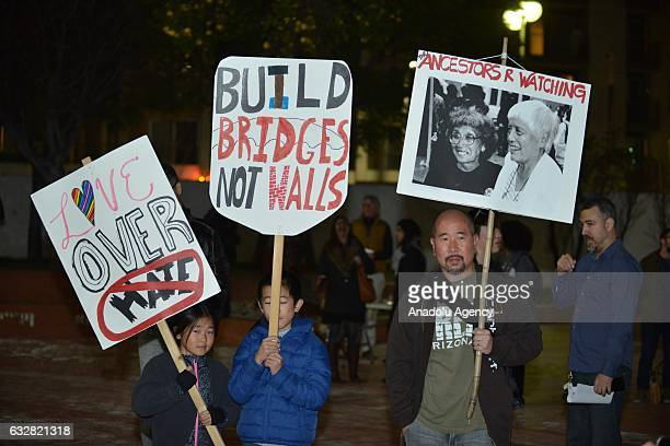 People hold banners during the candlelight vigil held to protest against President Donald Trump's decision for a wall between Mexico and US borders...